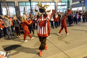 "Bucky Badger giving the Wisconsin ""W"" symbol with his hands at the 2016 Homecoming Parade"