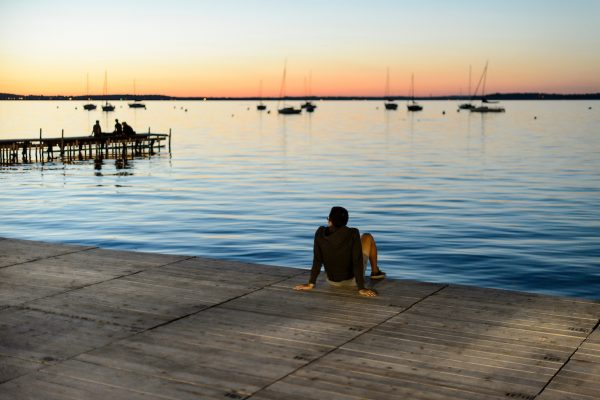 Student staring out at Lake Mendota from the Memorial Union Terrace at sunset